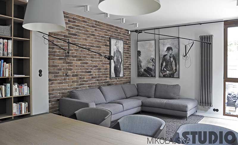 Salon z szarym narożnikiem i ceglaną ścianą