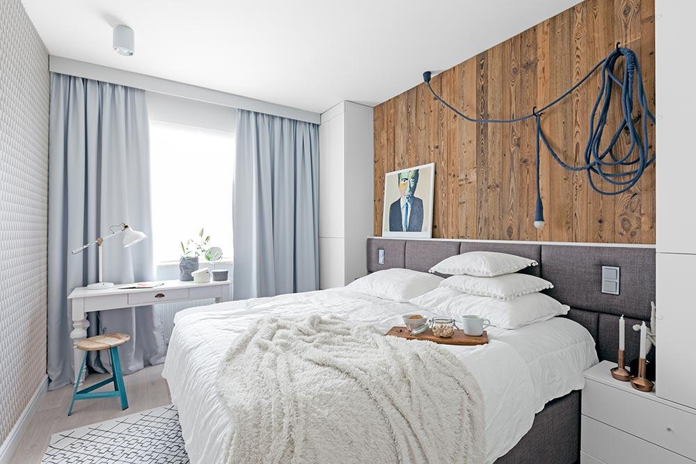 Sypialnia z drewnianą ścianą za łóżkiem