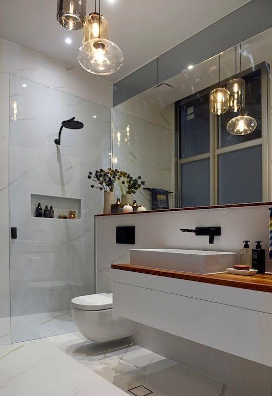 Biała łazienka z oświetlenie od Brokis