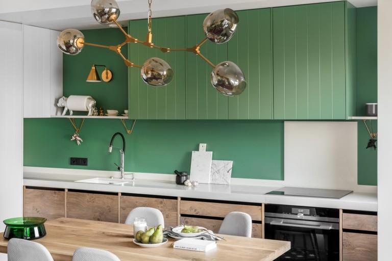 Drewniana kuchnia z elementami butelkowej zieleni i złota | proj. Finchstudio