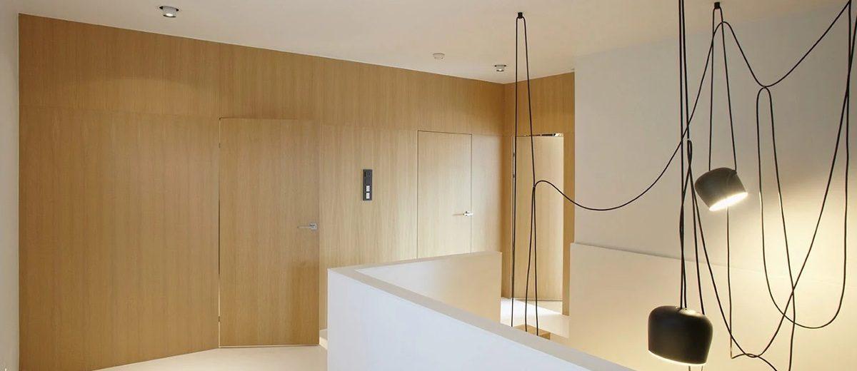 Klatka schodowa z charakternymi lampami w loftowym klimacie, proj. Ev Architects