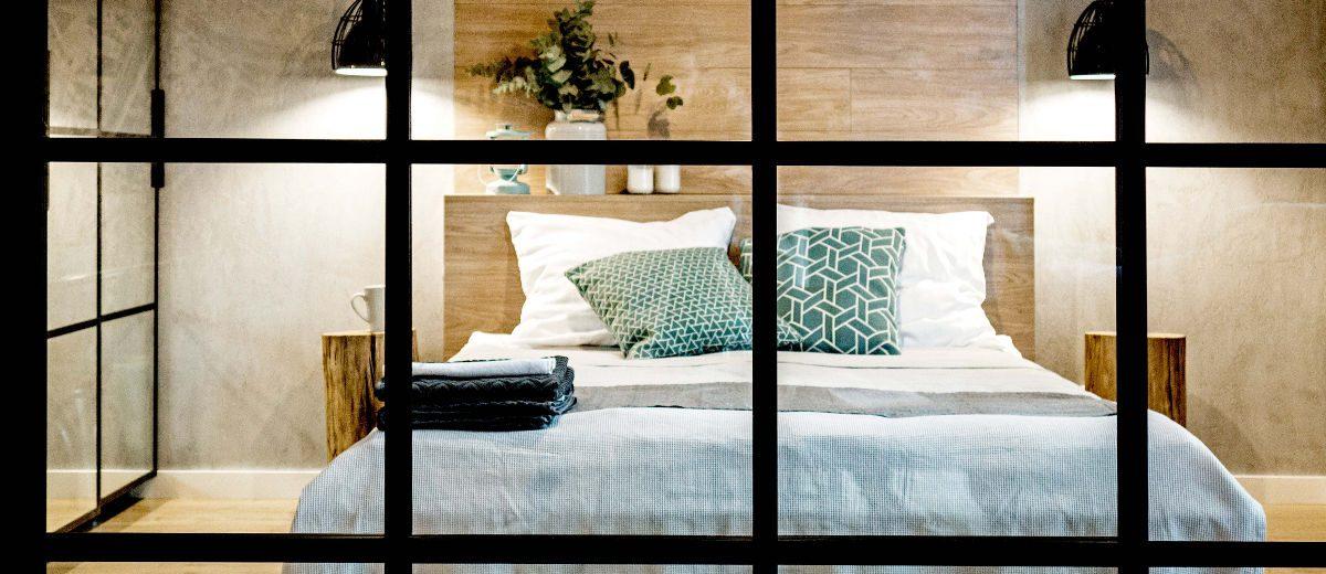 Widok na sypialnię za industrialnym przeszkleniem, proj. Mikołajska Studio