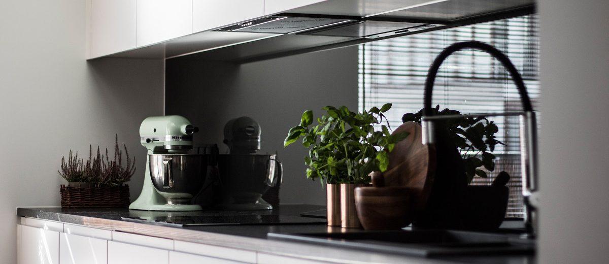 Białe meble kuchenne z czarną ścianą nad blatem | proj. TK Architekci
