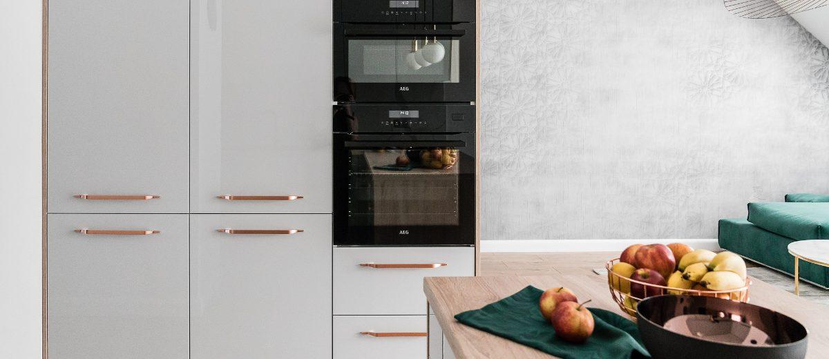 Meble kuchenne z popielatymi frontami na wysoki połysk i złotymi uchwytami | proj. Studio Projekt (zdjęcie: Fotomohito)