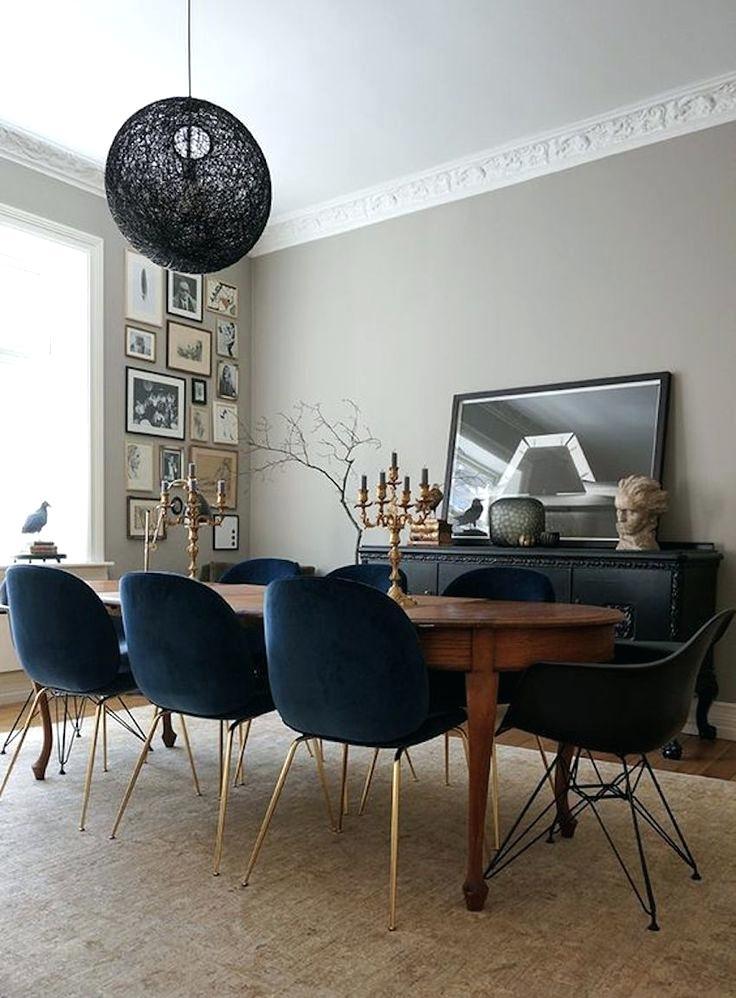 Welurowe granatowe krzesła w towarzystwie stylowego drewnianego stołu