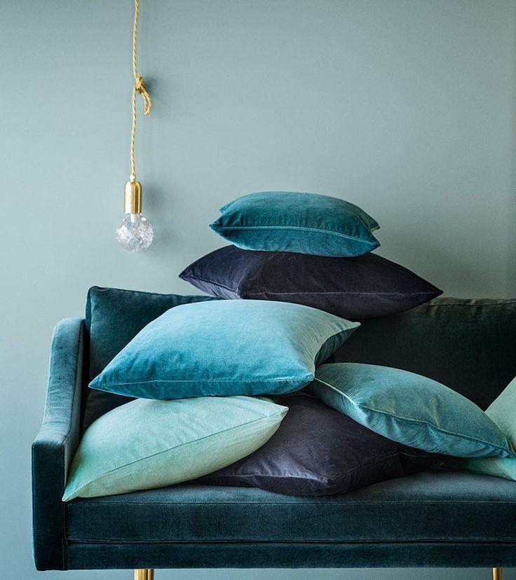 Poduszki welurowe w kolorze niebieskim, grancie i turkusie, sprawdzą się w towarzystwie zielonej sofy
