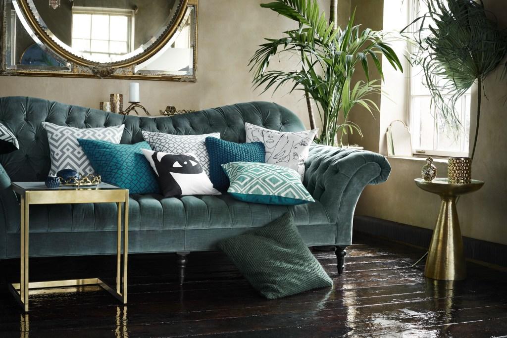 Welurowa zielona sofa w towarzystwie świetnie dobranych poduszek