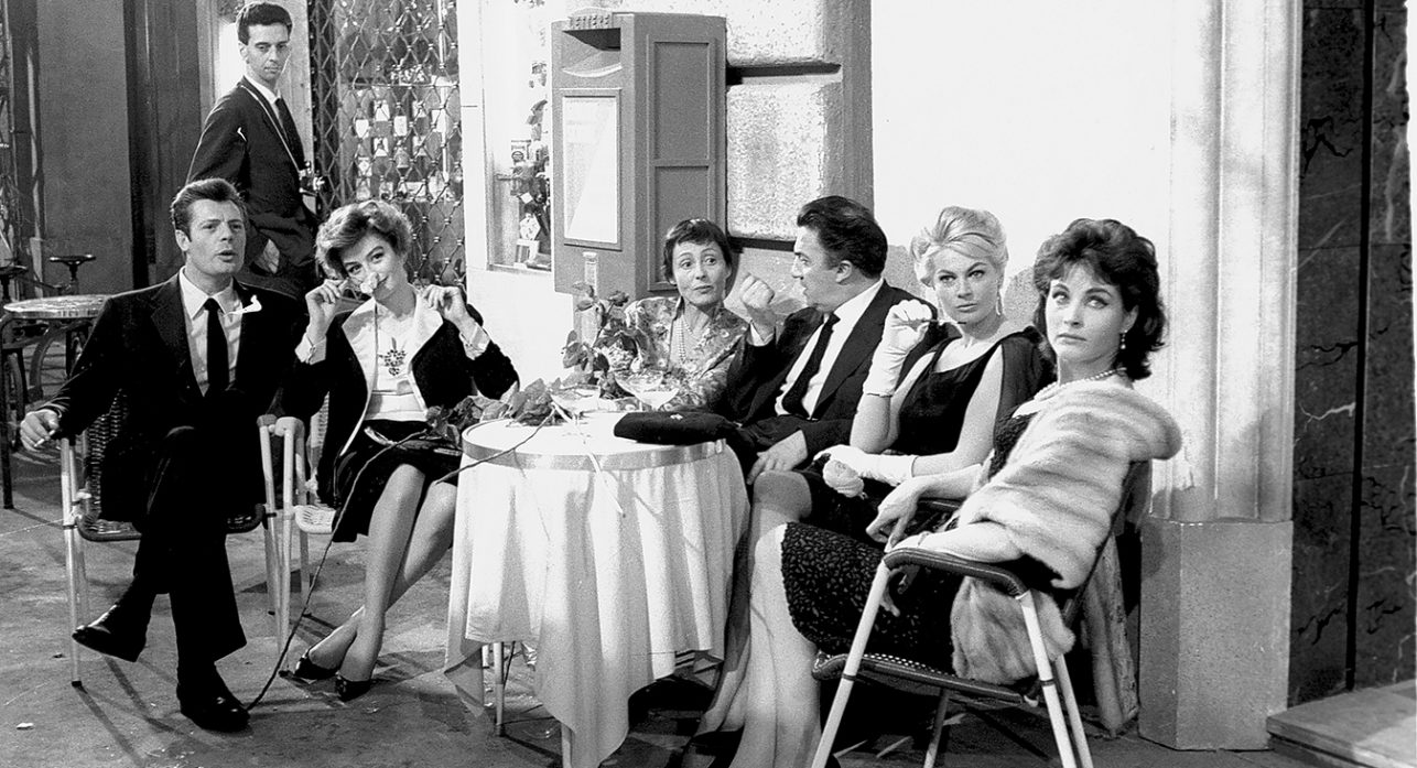 Italian film director Federico Fellini at the cocktail party for 'La Dolce Vita' in Cinecittà with actor Marcello Mastroianni (left), actresses Anouk Aimée, Luise Rainer, Anita Ekberg and Yvonne Furneaux. (Photo by Archivio Cicconi/Getty Images)
