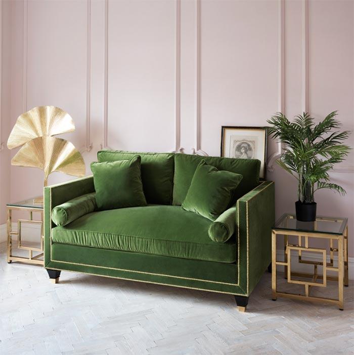 Zielona sofa na tle rózowej sciany