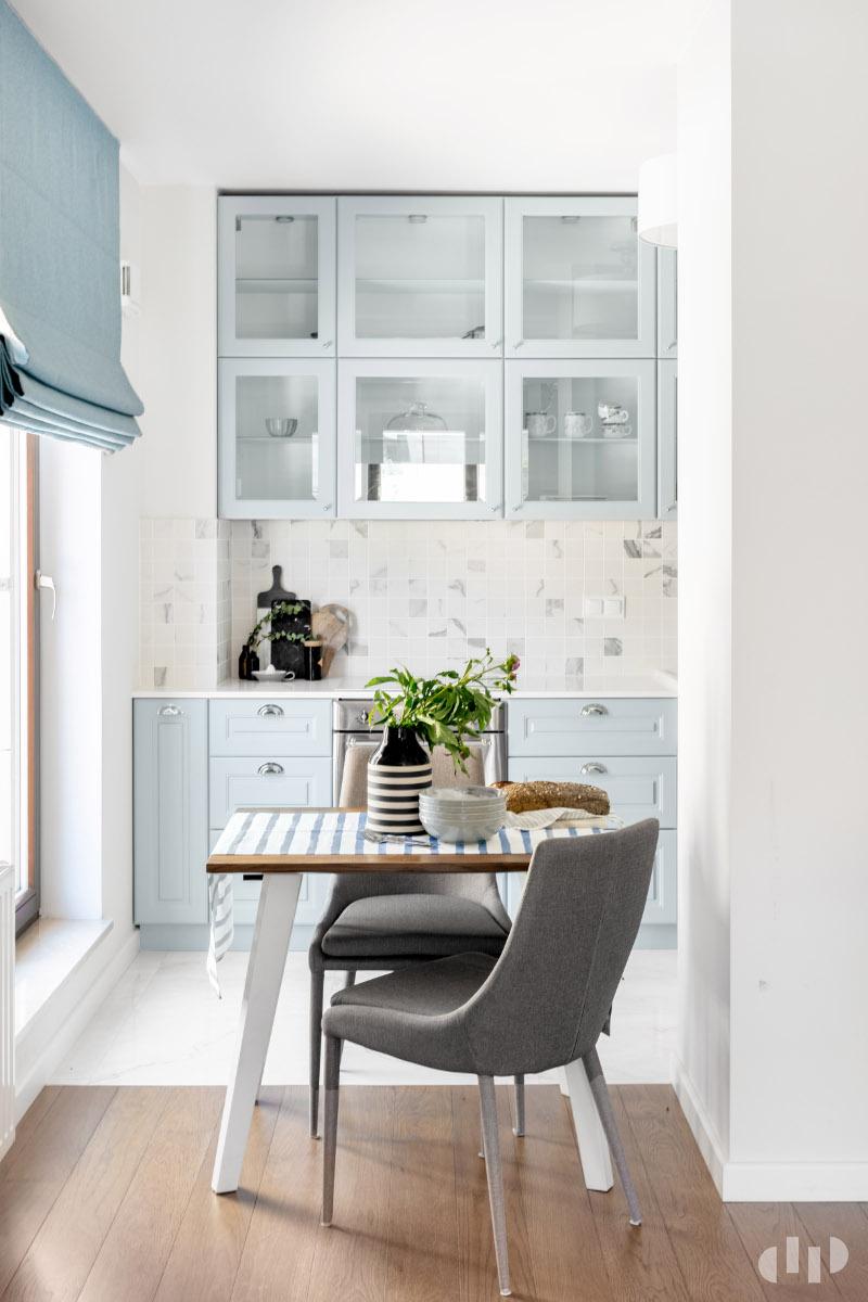 Mała kuchnia z błękitnymi meblami i marmurowymi płytkami nad blatem | proj. Dziurdzia Projekt