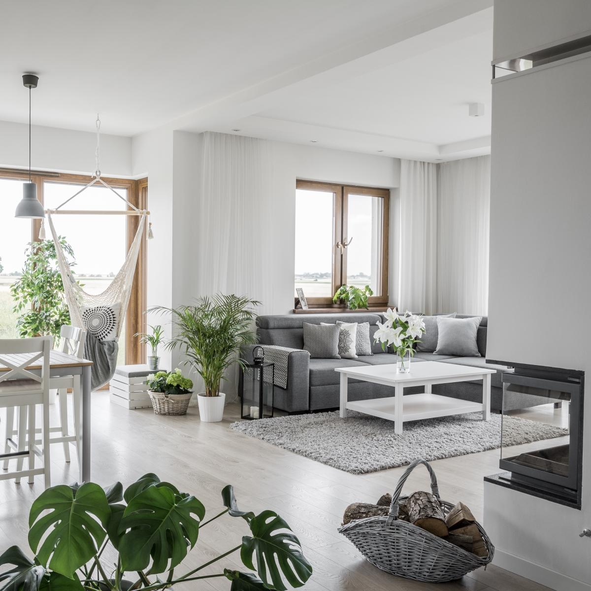 Salon z minimalistycznym kominkiem narożnym, wbudowanym w ścianę | Źródło @tam_i _tu
