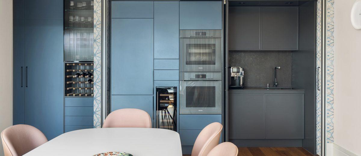 Granatowo - szare fronty zabudowy kuchennej doskonale korespondują z pastelowym różem