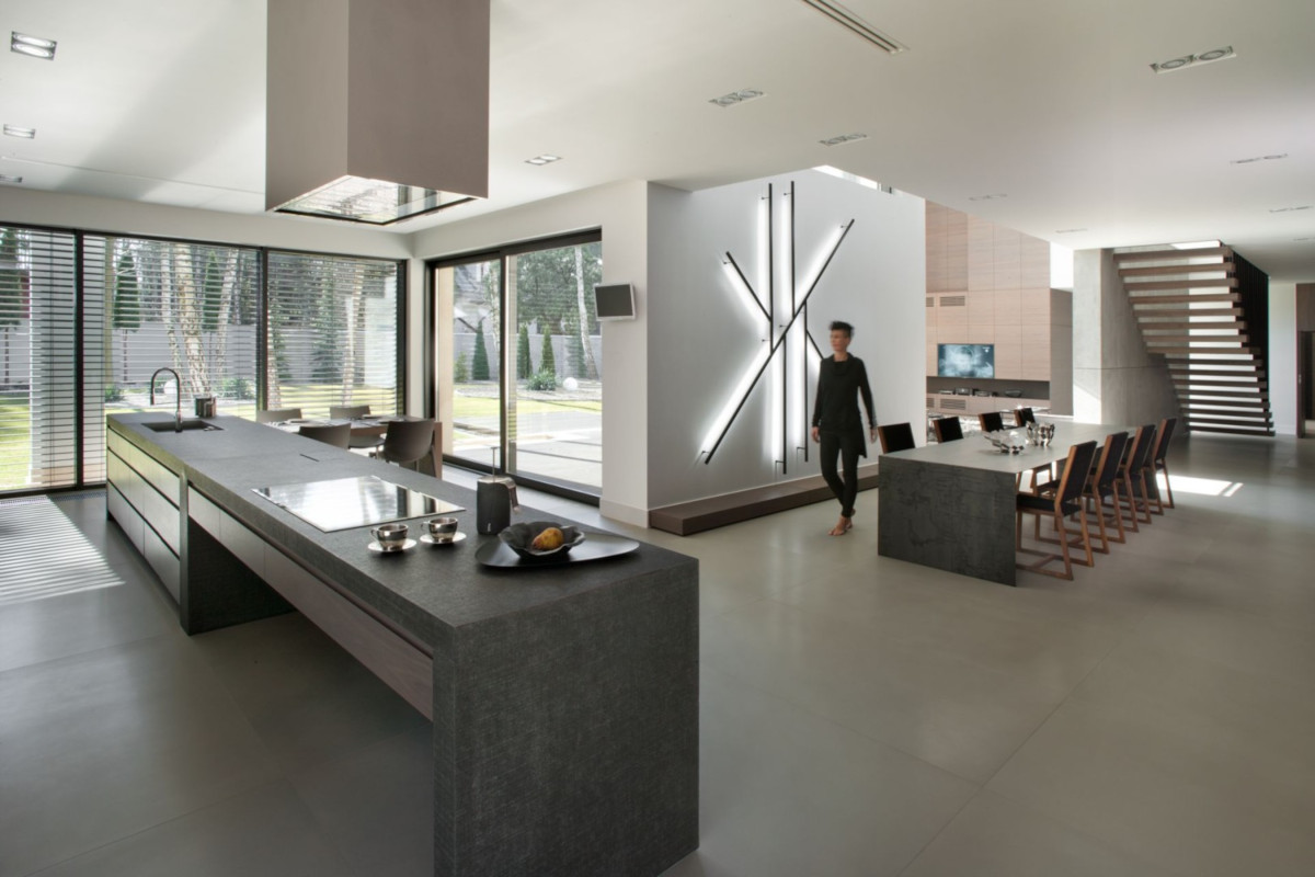Szare płytki na podłodze w kuchni, jadalni i salonie uspójniają projekt (Exit Design)