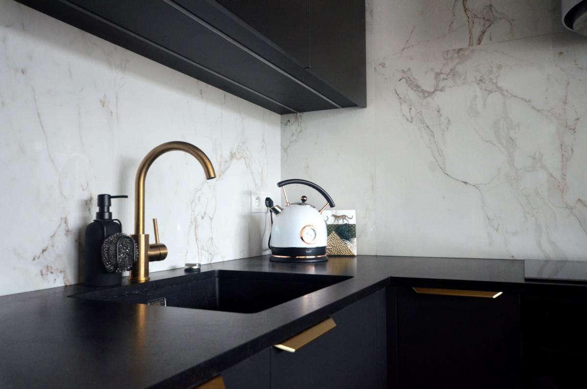 Złote detale w czarnej kuchni podkreślone eleganckim marmurem | proj. Soma Architekci