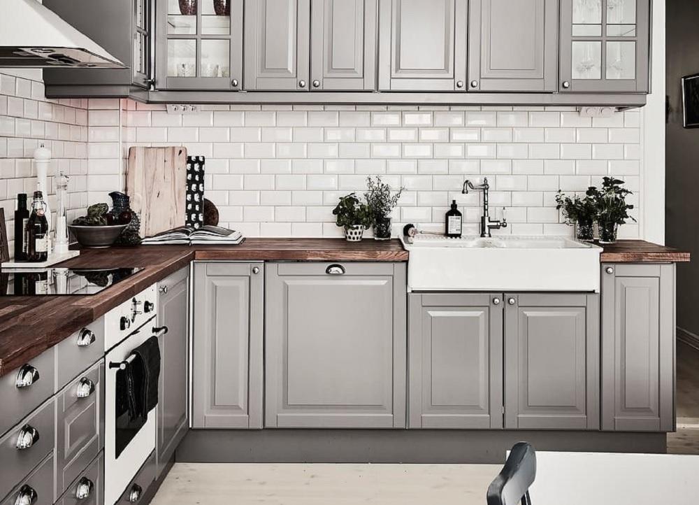 Szara kuchnia z drewnianym blatem i płytkami typu metro