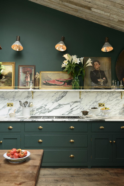 Zielona kuchnia bez szafek góenych z dodatkiem marmuru i złota