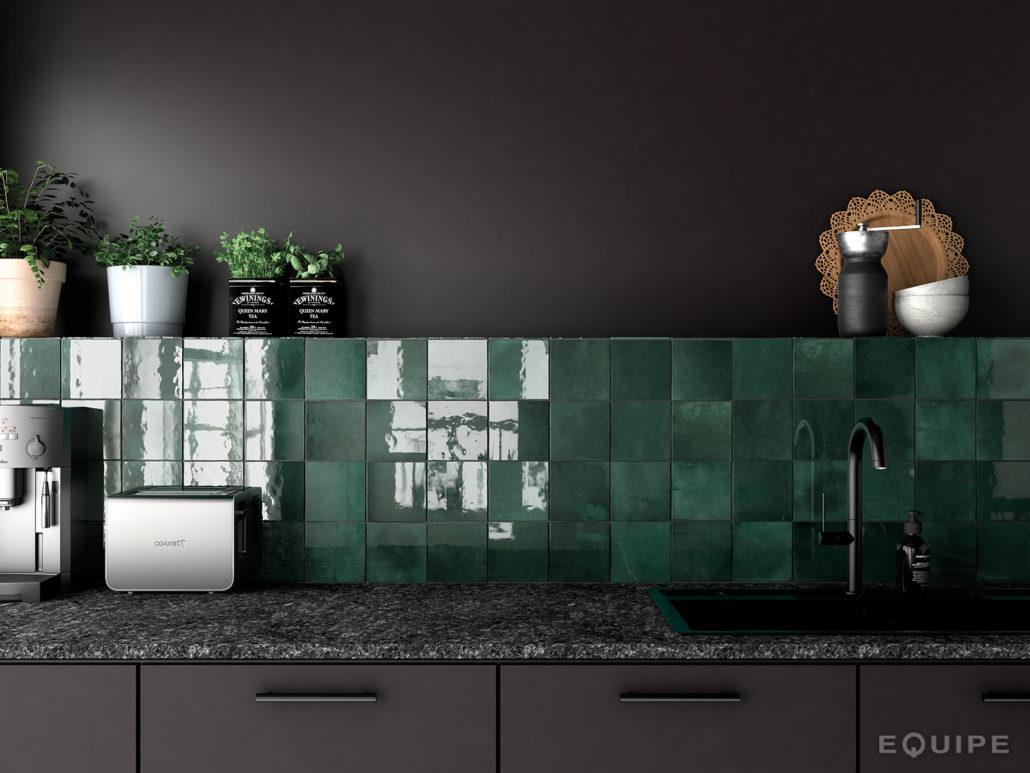 Połyskujące płytki w kolorze butelkowej zieleni na ścianie nad blatem w kuchni