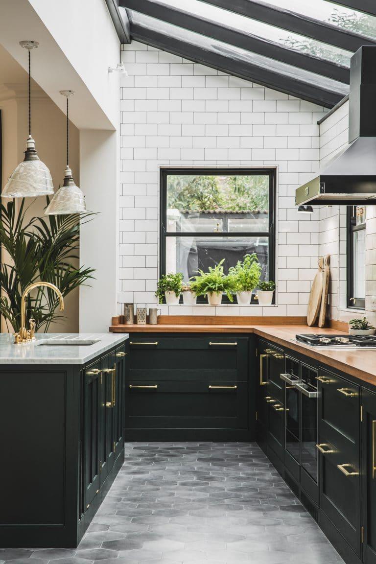 Tradycyjne białe kafle na ścianie nad blatem w kuchni pięknie grają z szarymi heksagonami na podłodze