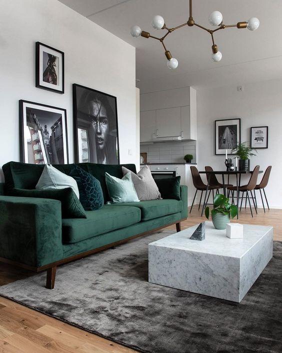 Aranżacja małego salonu w bloku: białe ściany uzupełnia sofa w butelkowej zieleni, szary dywan i złota oprawa wisząca. Charakteru wnętrzu dodaje mini galeria za wypoczynkiem.