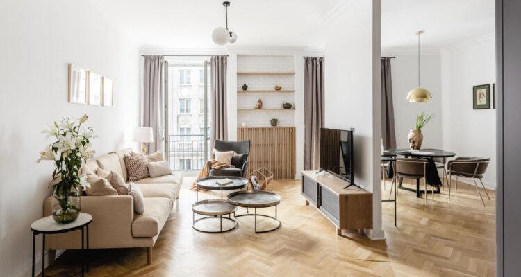 Salon w neutralnych kolorach z dużą ilością jasnego drewna i złotych detali | proj. Dziurdzia Projekt