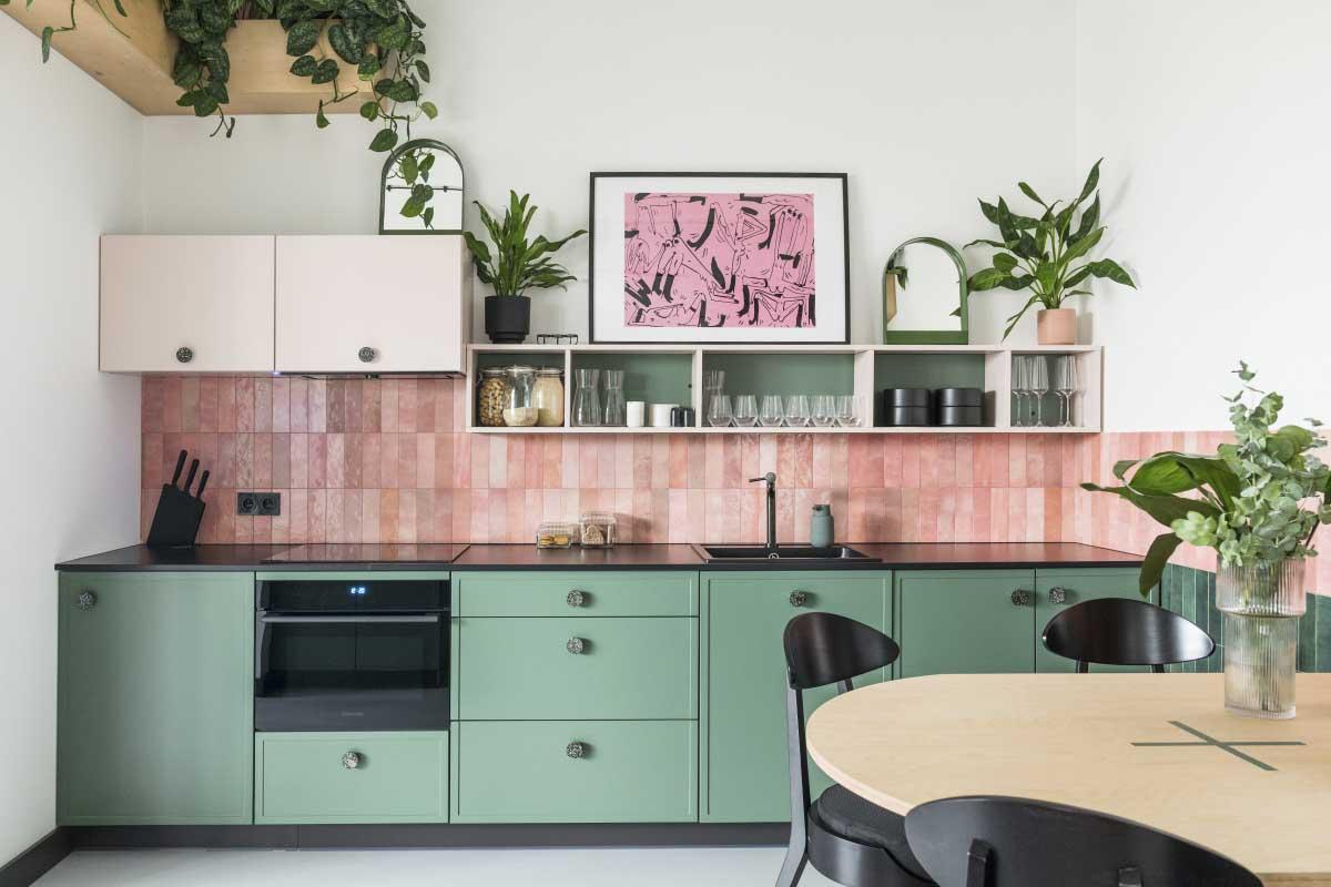 Pastelowo różowe płytki na ścianie nad blatem w zielonej kuchni | proj. Na antresoli