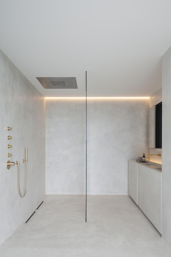 Odpływ liniowy w minimalistycznej łazience ze złotą aramaturą