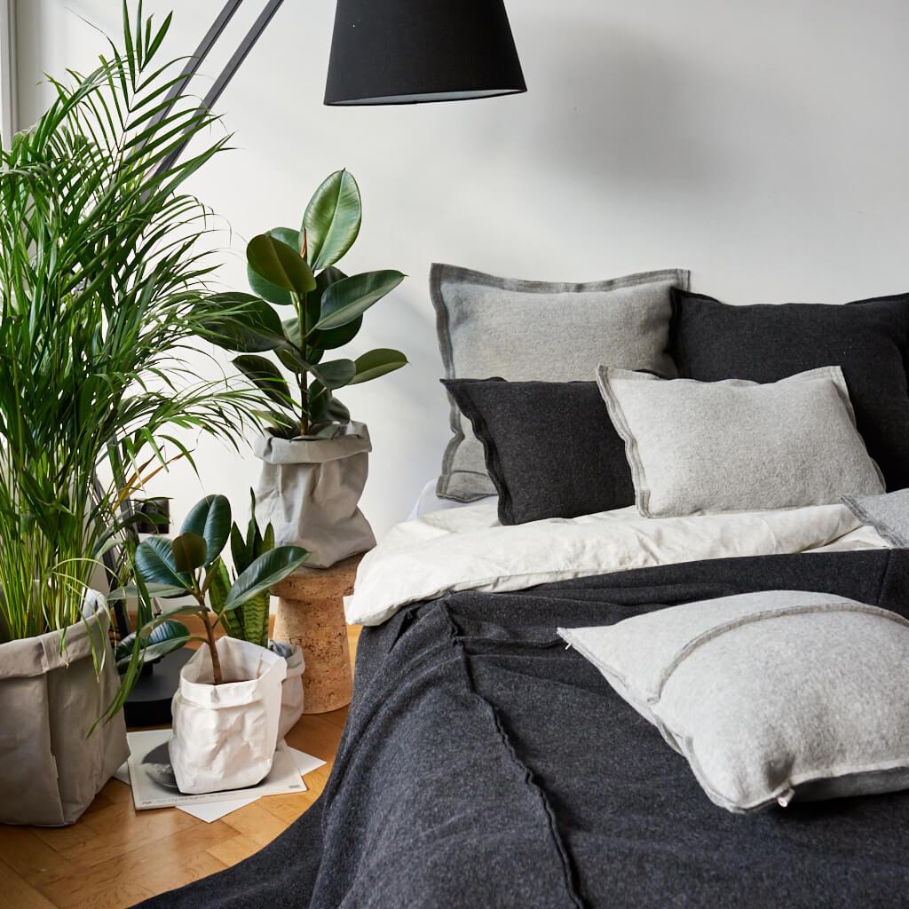 Naturalna sypialnia z dużą ilością roślin i naturalnymi tekstyliami od Moyha