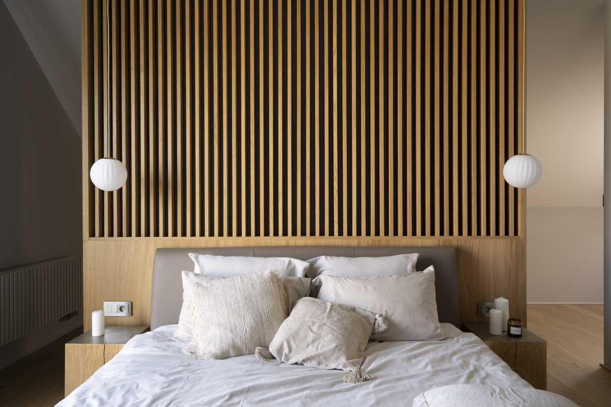 Ażurowa ściana z drewnianych szczebelek za łóżkiem w sypialni | proj. Na Antresoli, zdj.  Bartek Rąkowski
