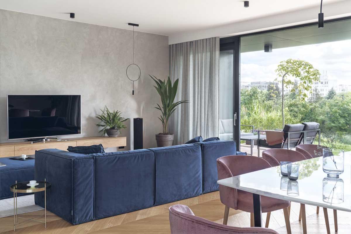 Betonowa ściana w salonie pięknie kontrastuje z przytulnym aksamitem na meblach | proj. luumo., zdj. Tom Kurek