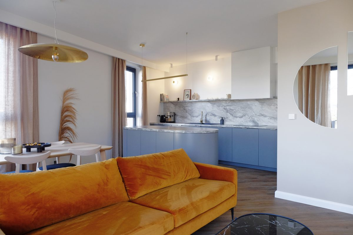 Meble kuchenne w kolorze Faded Denim zestawione z welurową sofą w odcieniu Orange Peel | Projekt Małgorzata Caban Architektura Wnętrz