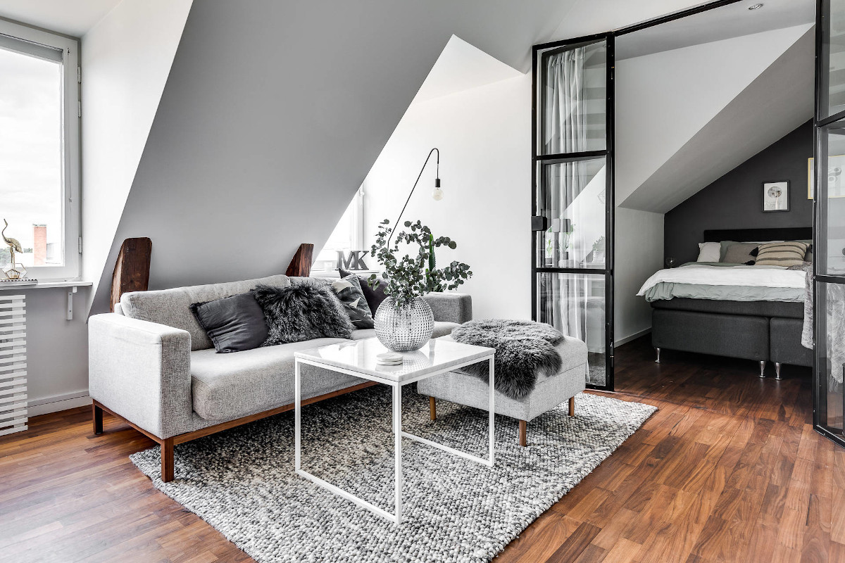 Piękny i funkcjonalny salon na poddaszu z przeszkloną sypialnią