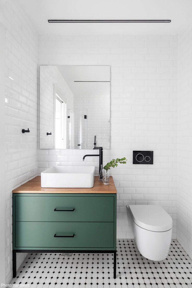 Zielona szafla podumywalkowa w białej łazience