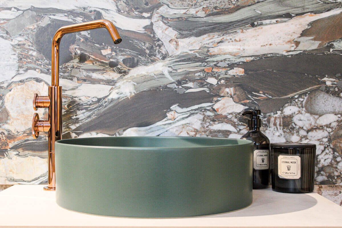 Zielona umywalka HushLab i bateria Geda na tle płytki wielkoformatowej | produkty dostępne w showroomach z Grupy Internity Home