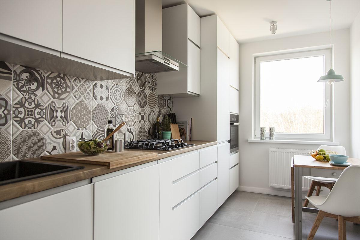 Szare płytki na podłodze w kuchni w zestawieniu z cementowymi na ścianie nad blatem